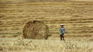 boy running in a field near the haystack, mown field and boy video