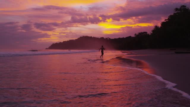 Boy running on beach at sunset video