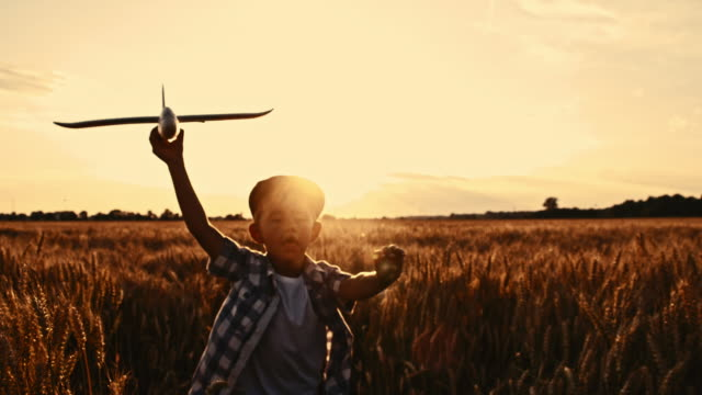 SLO MO Boy running with airplane in wheat field video