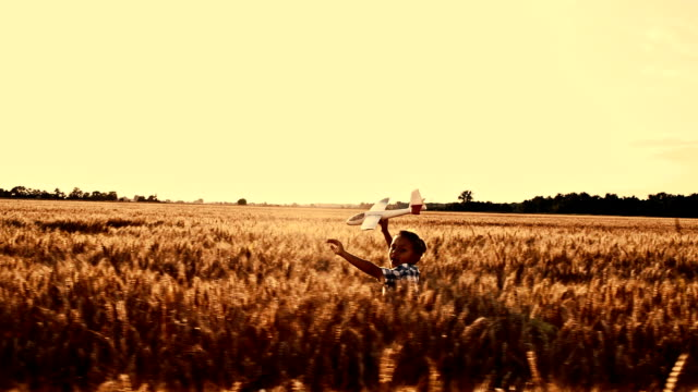 SLO MO Boy running with airplane toy in wheat field video