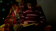 boy showing his grandmother a book sitting in a chair video