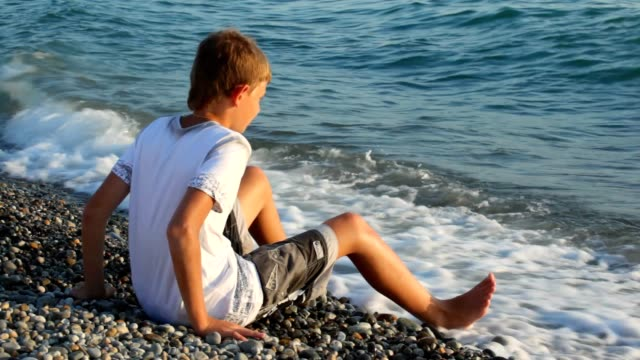 Boy sits on pebble beach and looks at sea video