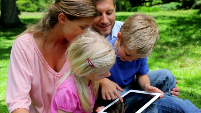 A boy sits with his family who watches as he presses the screen of a tablet pc video