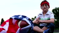 Boy sitting next to American football ball with us national flag video