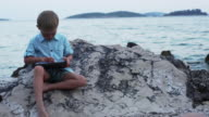 Boy sitting on the rocky shore. video