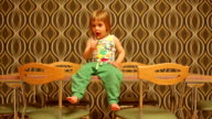 boy sitting on the table and it lollipop. video
