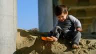 Boy Sliding Down Sand Under a Pier video