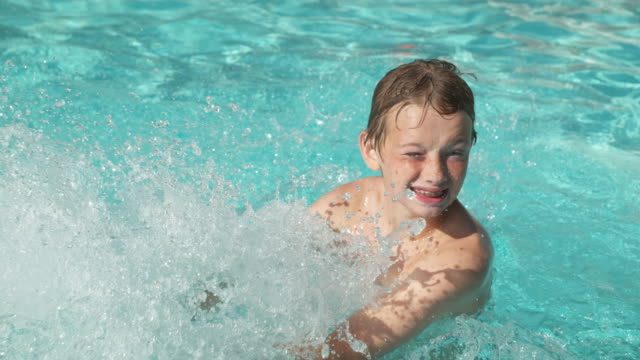 Boy splashing in pool, video