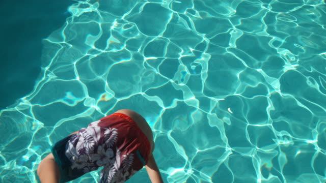 Boy splashing into pool in slow motion video