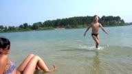 Boy splashing on the beach video