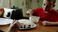 A boy spreading cream on the top of a cake. video