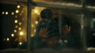 Boy spying on Santa-Claus distributing presents under christmas tree video