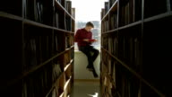 boy -  student reading a book on a window sill at the library video