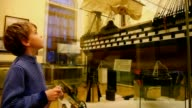 Boy take good look on model of boat in museum video