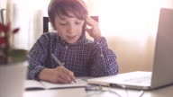 Boy talking on cell phone and writing notes video