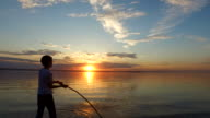 Boy teenager coached by kick a long stick. The boy stands on the shore of a large lake. video