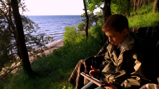 Boy teenager sitting on a chair on the shore of a large lake. Teen Boy enthusiastically playing a computer game on a Tablet PC video