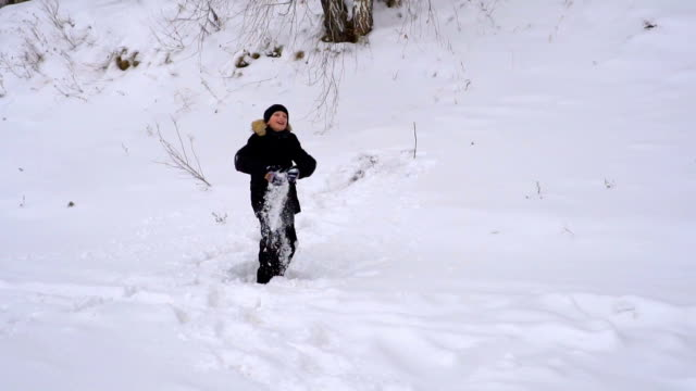 Boy teenager throws up fresh snow. The boy very happy the come winter. Winter cloudy day. Slow motion. video