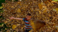 Boy throwing fall leaves, slow motion video