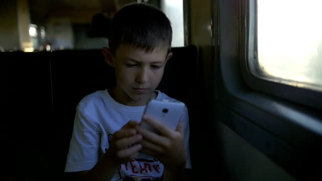 boy travelling by train sitting in wagon using mobile phone, slow motion video