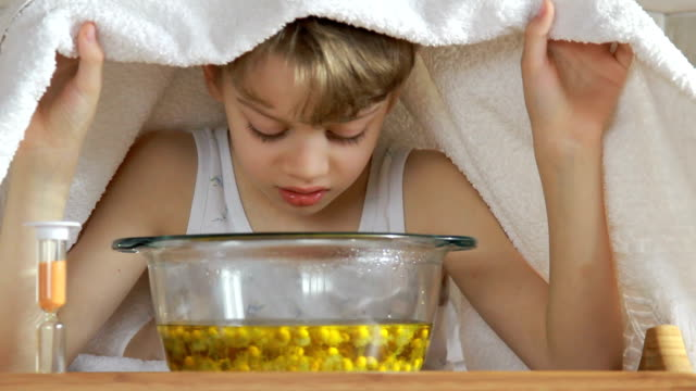 boy under towel breathes balsam vapors to treat colds video