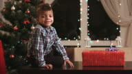 Boy unwrapping gift on table. video