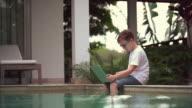 Boy using a laptop sitting near pool video