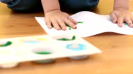 Boy using his hands to make painted handprints video