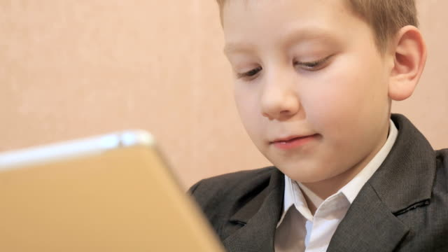 Boy using tablet computer and smileing video