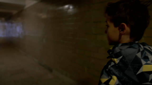 Boy walking alone in a narrow tunnel in the city, back view video