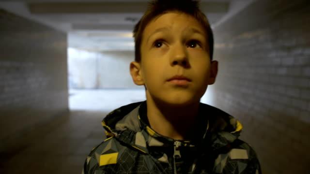 Boy walking alone in a narrow tunnel in the city video