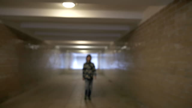 Boy walks through an unfamiliar tunnel in the city, a deserted place, a teenager in blue ragged jeans and a jacket, with a hood on his head, a dirty tunnel, the teenager is cautious, serious looking, looks straight video