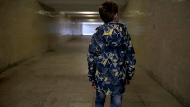 Boy walks through the tunnel, goes to the exit from the tunnel video