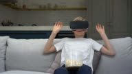 Boy watching a movie with vr glasses and eating popcorn video