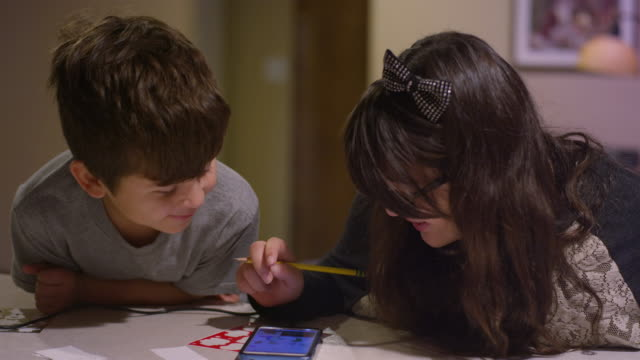 A boy watching his sister as she draws and looks through her phone for inspiration video