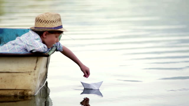 Boy wearing wicker hat sitting in the boat setting his paper boat on a journey video