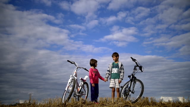 boy with a girl holding hands, standing against the sky with bicycles video