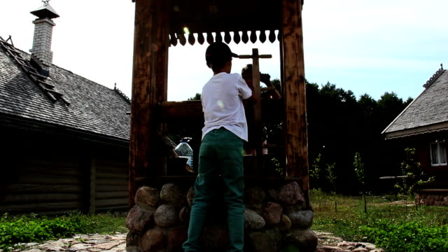 boy with a girl pull out a bucket of water from a well in the Russian village video