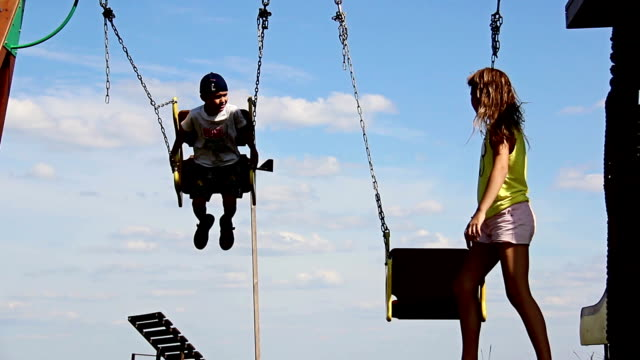 boy with a girl swinging on a swing, a swing with an iron chain video