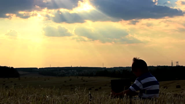 boy with a laptop in a field at sunset, boy working on a laptop at sunset on top video
