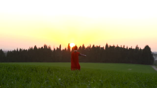A boy with a superhero cape in a green field during sunset video
