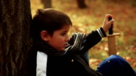 Boy with a sword resting in autumn forest under a tree video