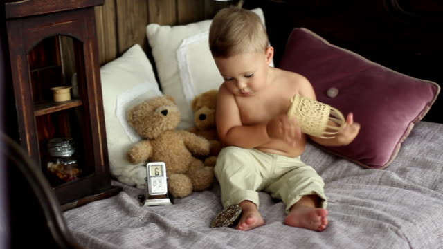 boy with a teddy bear on a bed video