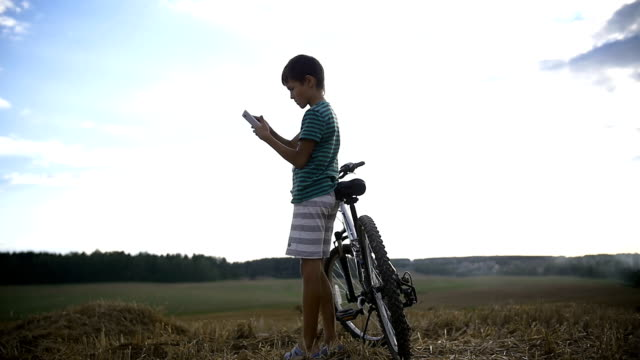 boy with bicycle uses the phone on the mountain video