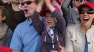 Boy with family in crowd of sports spectators video