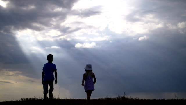 Boy With Girl Walking and Holding Hands on a Background of Clouds in the Morning video