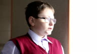 boy with glasses looking out the window video