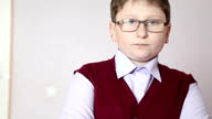 boy with glasses standing against a wall video