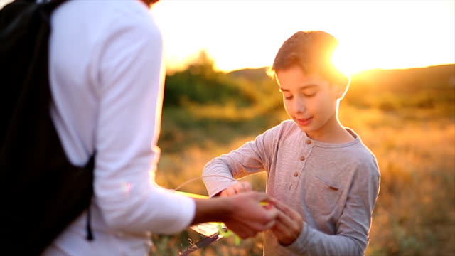 Boy with his father prepares to fly a kite at sunset video