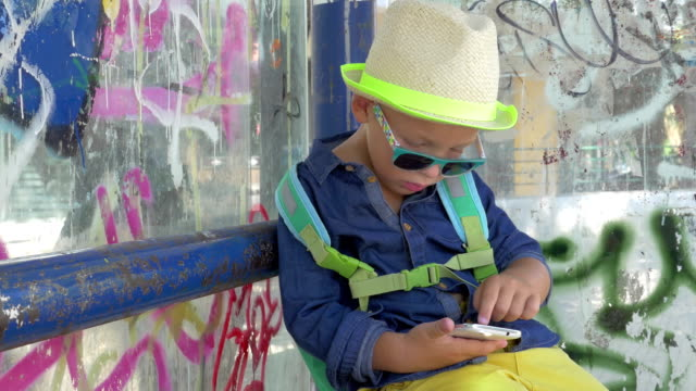 Boy with smartphone at grungy city bus stop video